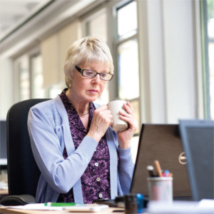 Woman drinking tea at computer