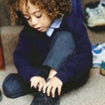 child putting on shoes
