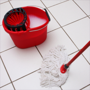 mop and bucket of soapy water on tiled white floor