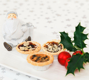 photo of mince pies next to small santa figure dressed in white