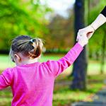 little girl holding mums hand