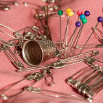 Close up ophoto of sewing pins, safety pins and a thimble on pink fabric