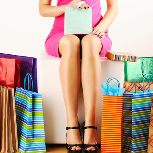 photo of woman in pink dress with black high heeled sandals surrounded by shopping bags