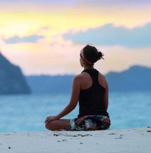 Lady meditating on beach