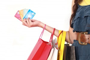 Credit cards in hand with shopping bags