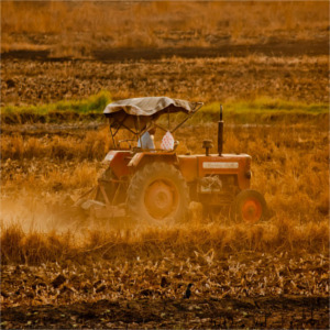farmer on tractor in soil field with dust clouds