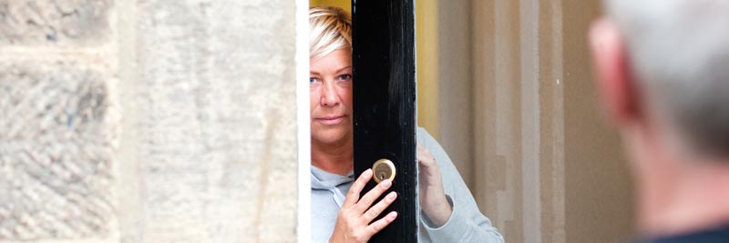 woman at door looking frightened